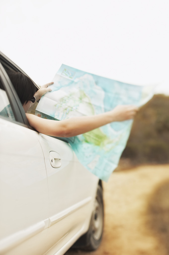 woman holding map out of car window