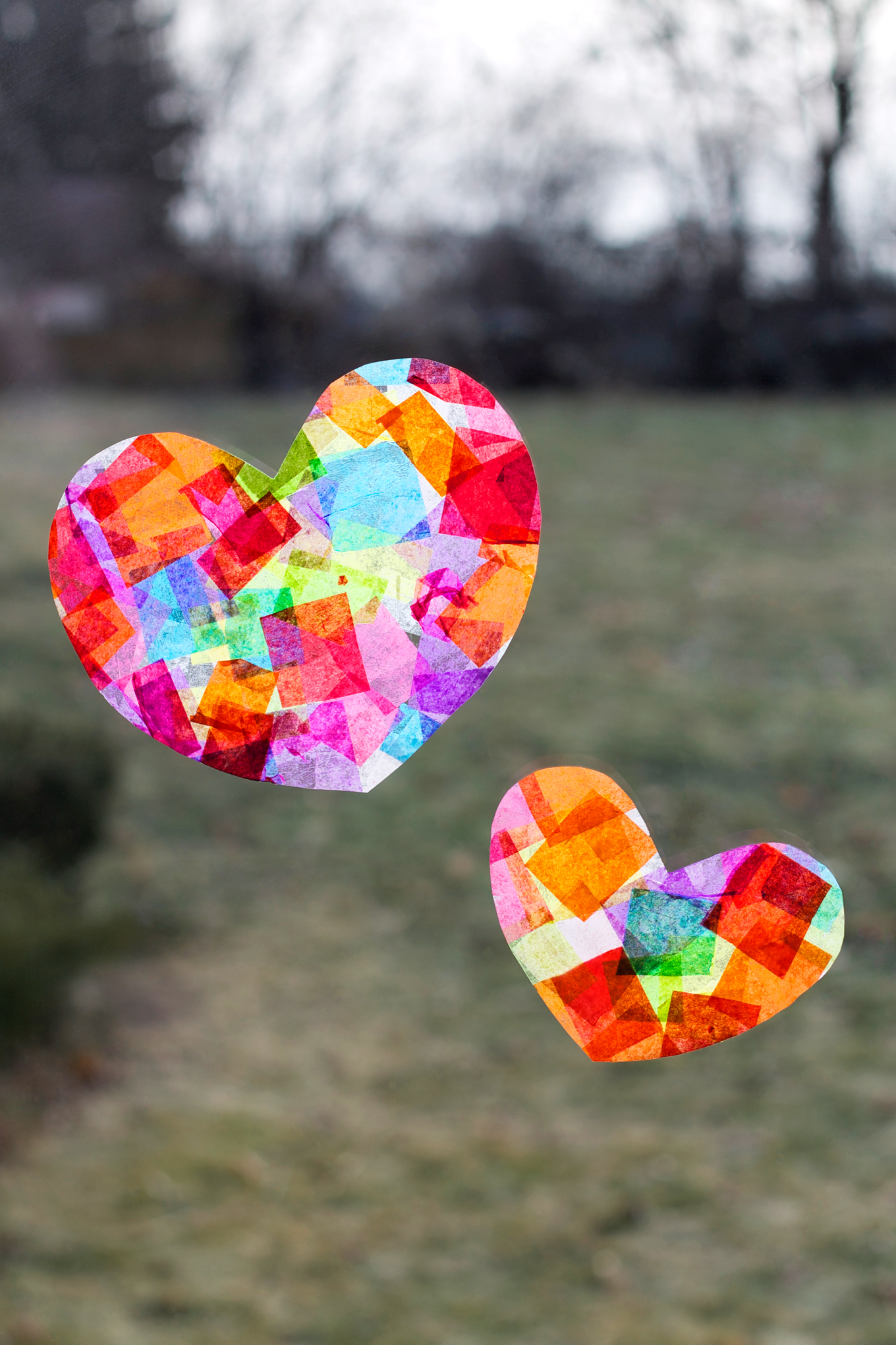 two hearts on a window made with colored tissue paper squares