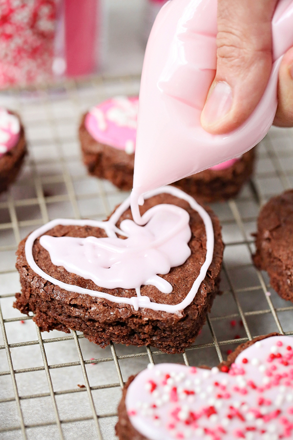 frosting a heart shaped brownie with a bag of pink icing