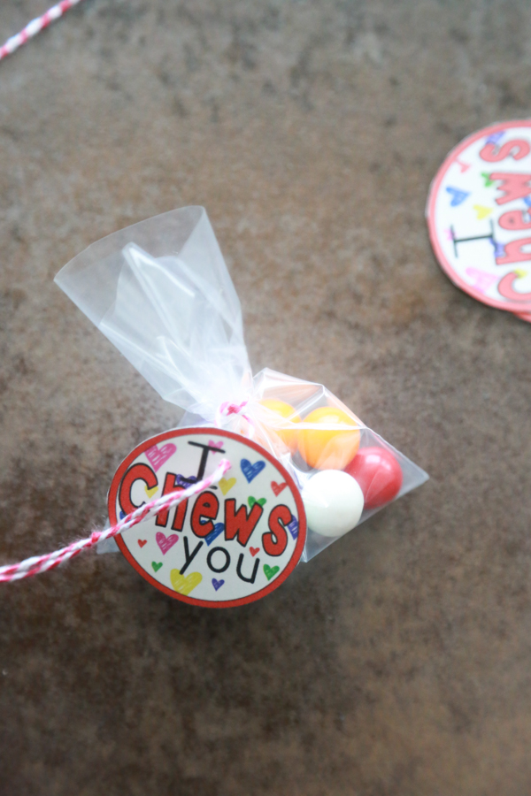 a bag of gumballs tied with red and white twine with the I Chews You printable