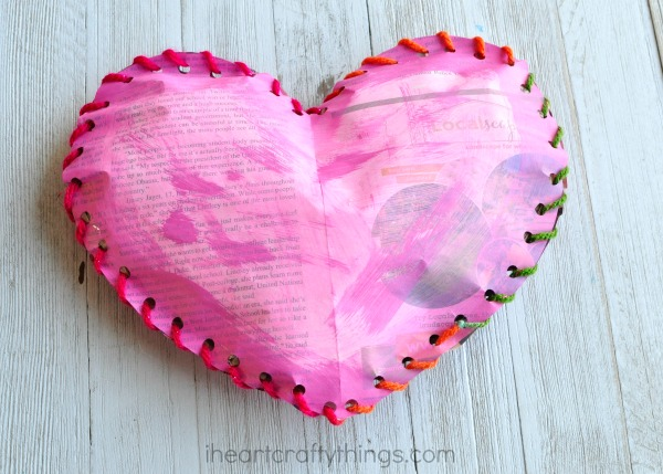 a pink heart made from old newspaper and yarn