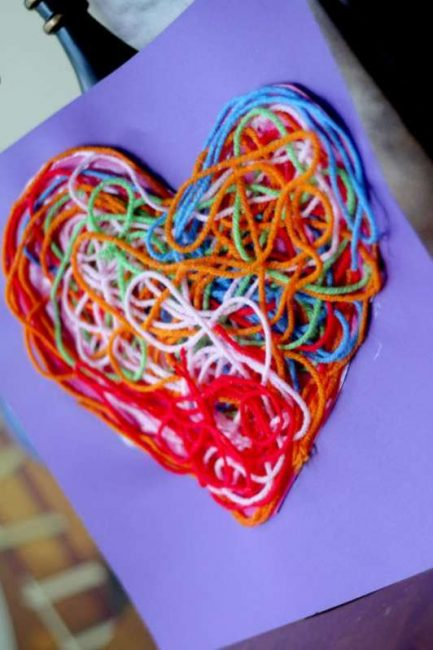 a heart made out of yarn glued onto a piece of construction paper