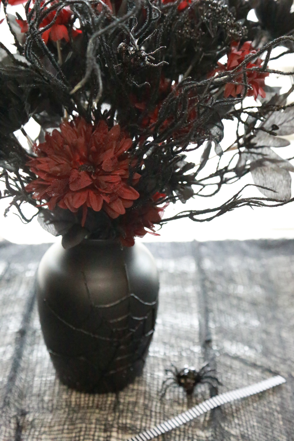 See how I transformed a $1 dollar store vase into a eerily beautiful DIY Spider Web Halloween Vase.