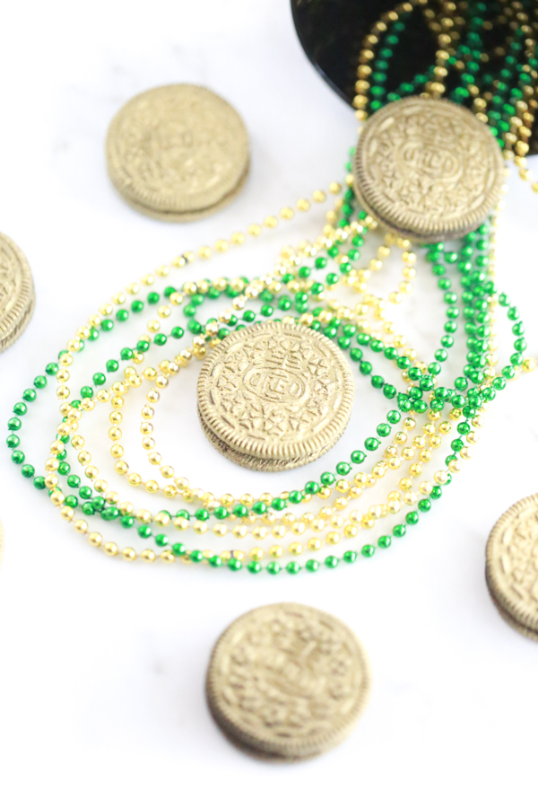 lots of edible gold oreos with gold and green bead necklaces