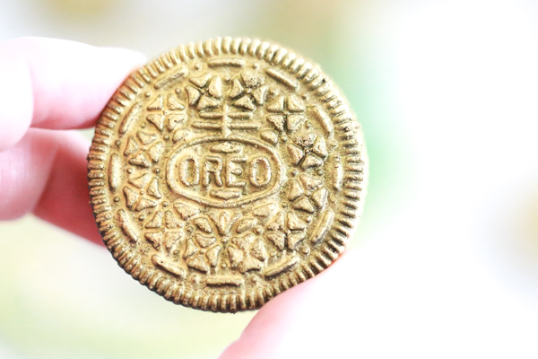 person holding gold covered oreo in their hand