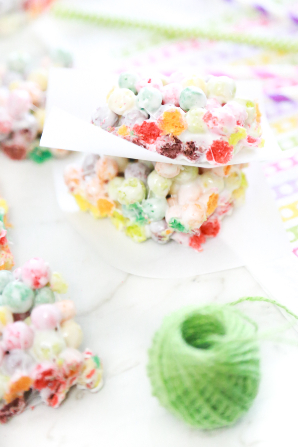 rainbow marshmallow treats stacked with a spool of green ribbon to the side