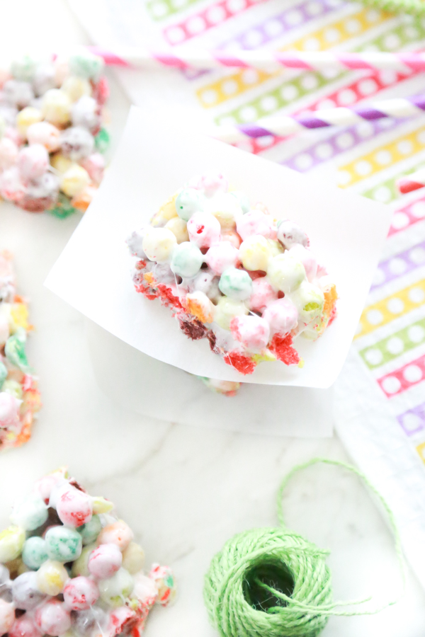 rainbow marshmallow treats on a white background with colorful napkin and green twine