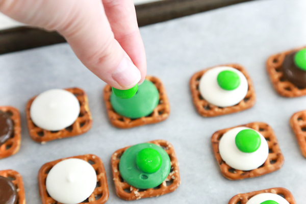 putting a green M&M on a candy melt on top of a waffle pretzel