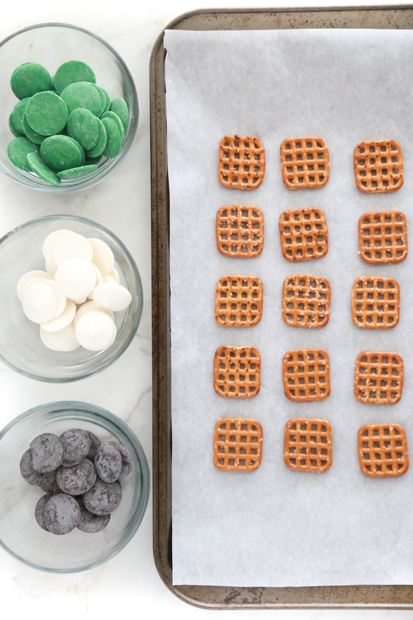 a tray of waffle pretzels with candy melts to make St. Patrick's Day Pretzel Bites
