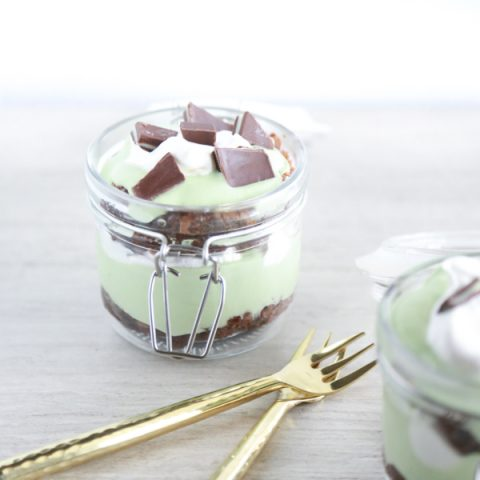 a glass jar filled with layer of brownie, cool whip and pudding to make a St. Patrick's Day Parfait