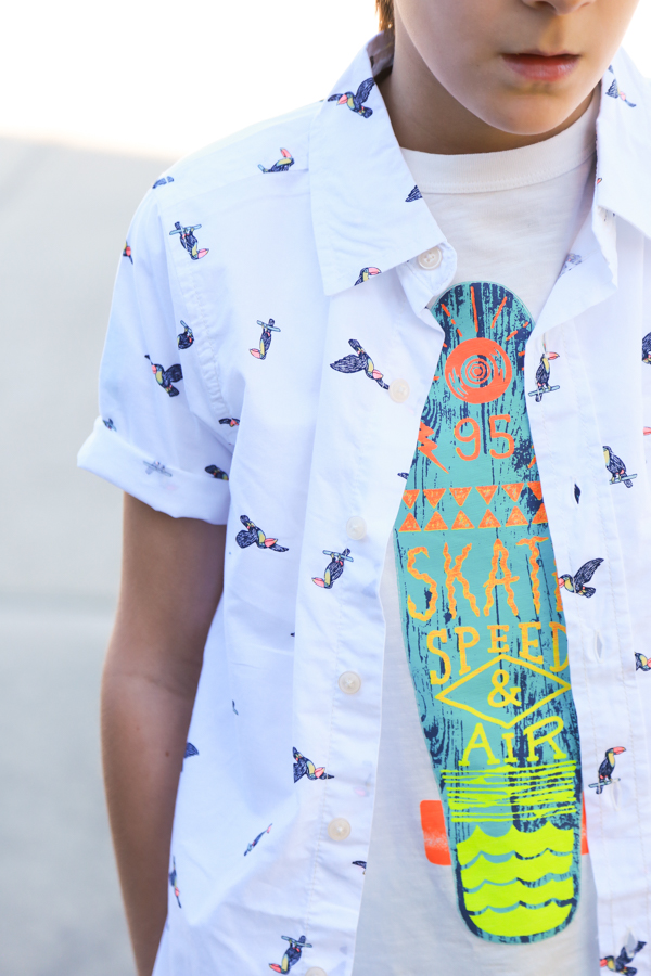 A little boy wearing a surf board shirt with a white button-up on top with toucans -perfect spring styles at oshkosh b'gosh
