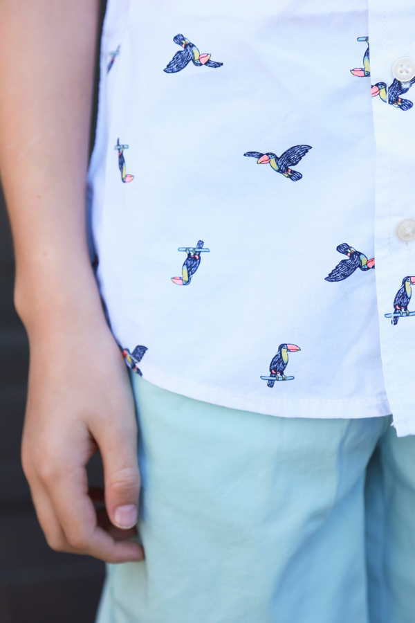 a child wearing blueish shorts with a white button up shirt with toucans on it - perfect spring styles at oshkosh b'gosh