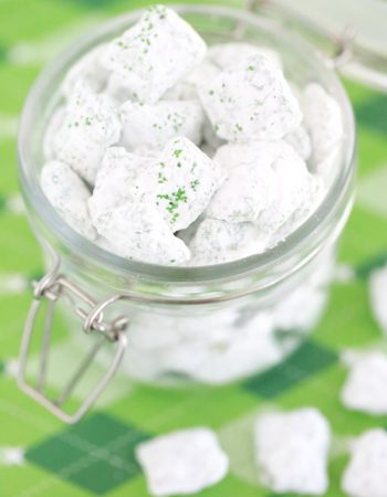 st. patrick's day puppy chow - rice chex mix covered in green candy melts, powdered sugar, and green sugar sprinkles