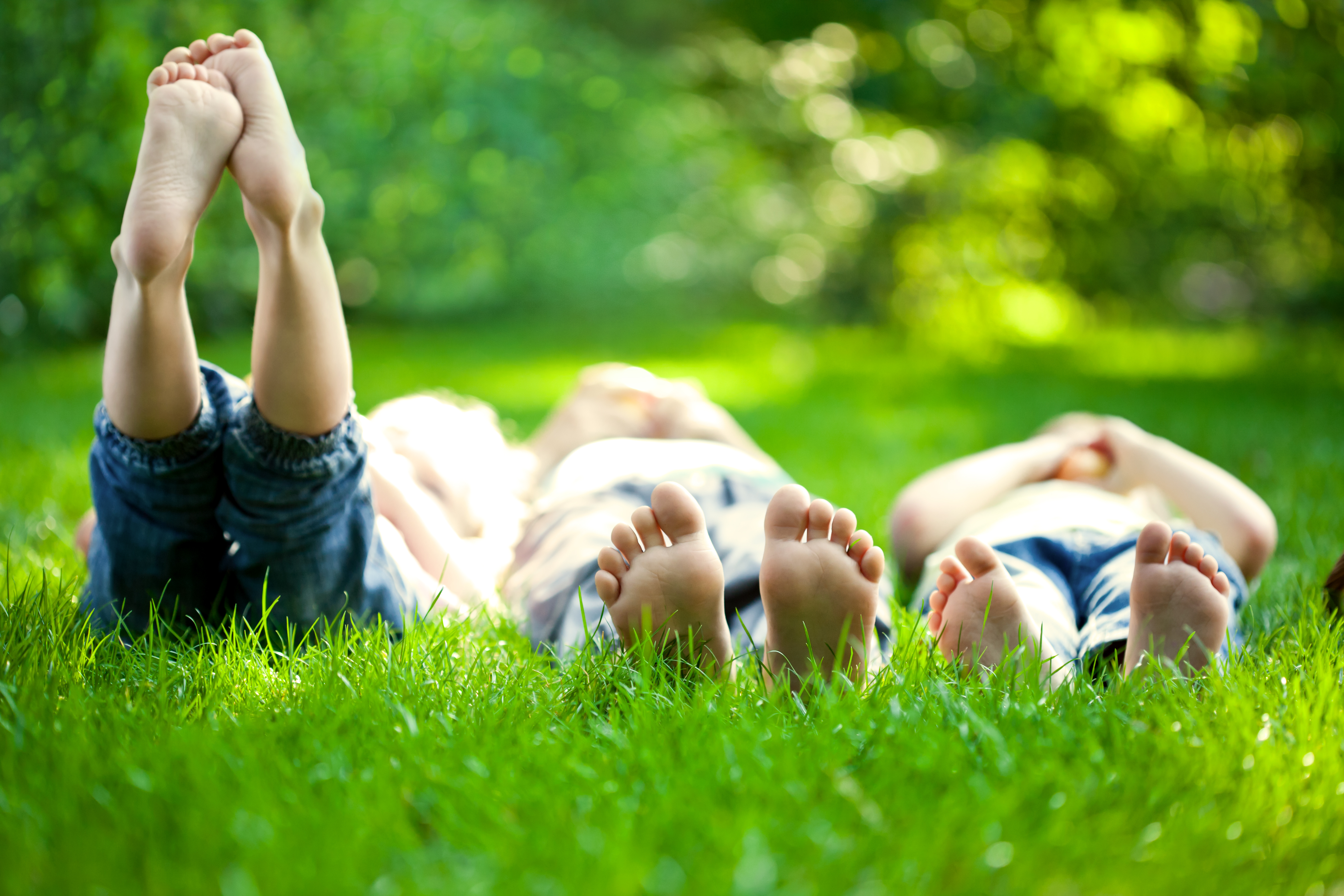 Group Of Hy Children Lying On Green Gr Outdoors In Spring Park