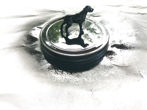 a glass lid with a dog figure glued on top and spray painted black to make the lid of a homemade dog treat jar